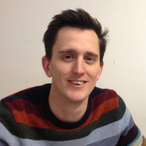 A man with brown hair wearing a striped jumper looking into the camera