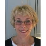 A blonde woman wearing glasses looking into the camera