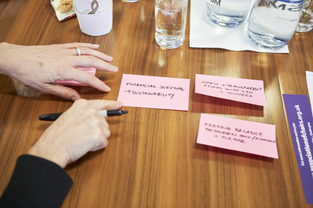 person writes post-it notes for discussion, includes finance, relationship with CEO etc