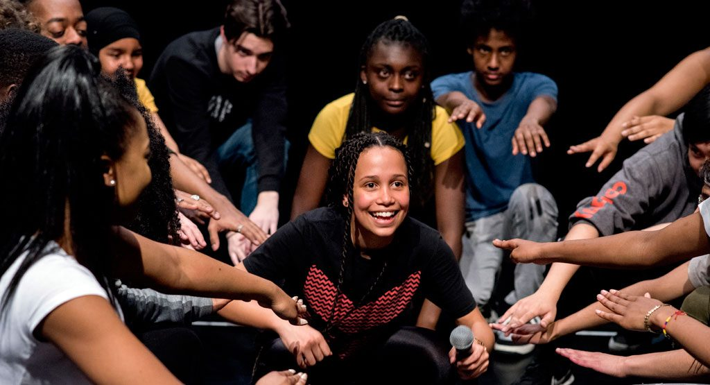 Young woman surrounded by a big group of other young people. Smiling. Drama workshop. Image from Company Three